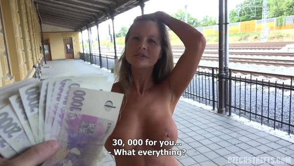 Mature woman is given money in a public place
